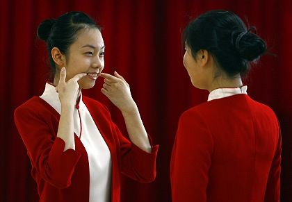 A student shows another how to smile during an etiquette training class at a vocational school in Beijing.