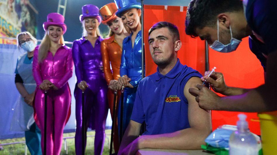 Ein junger Mann erhält in der britischen Stadt Halifax während einer Zirkusvorstellung eine Coronaimpfung