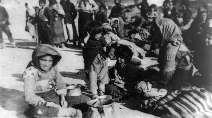Eine Gruppe armenischer Flüchtlinge sitzt 1915 in Syrien auf dem Boden.