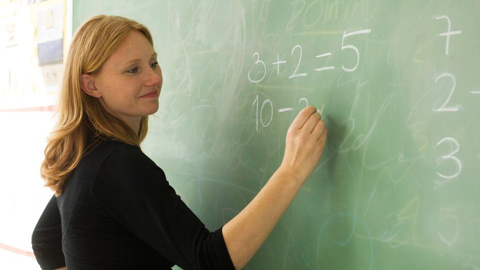 Grundschullehrerin an der Tafel: Positive Grundeinstellung zu Beruf und Schülern