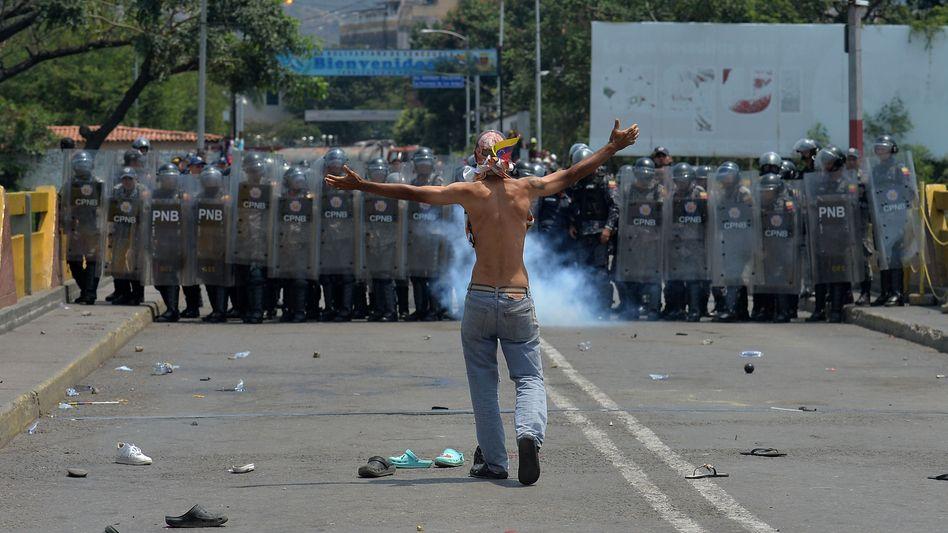 Ein Demonstrant vor Sicherheitskräften