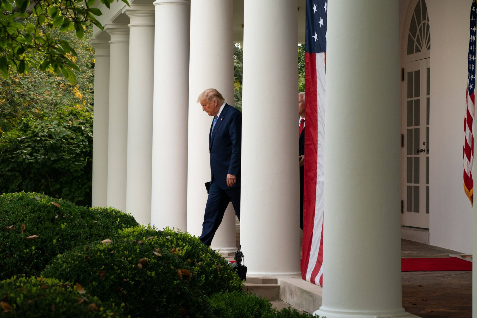 United States President Donald Trump walks out to the Rose Garden with United States Vice President Mike Pence to give