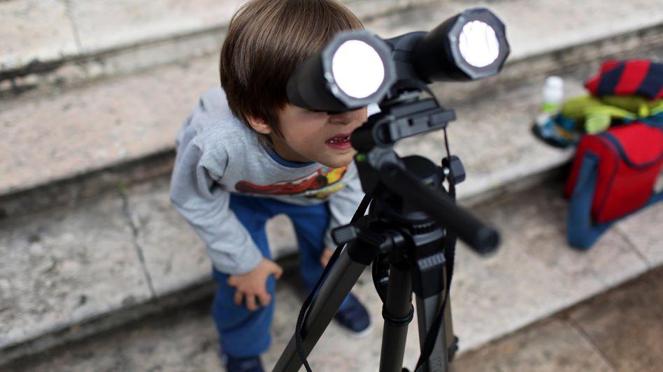 Ein Junge guckt durch ein mit Filtern ausgestattetes Fernglas: Diesen Freitag ist Sonnenfinsternis