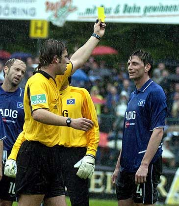 Robert Hoyzer gives a yellow warning card to Hamburg's Bastian Reinhard during the first round of the German Cup match between SC Paderborn and Hamburg SV in August. Hoyzer admitted he manipulated the game to help Paderborn win.