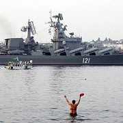A swimmer welcoming a Russian cruiser back to port in Sevastopol as it returned from Georgia a week ago.