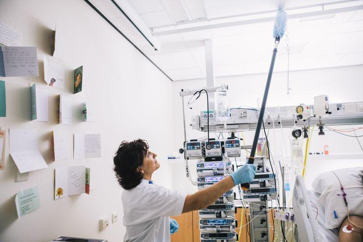 Eine Reinigungskraft säubert ausgiebig ein Patientenzimmer auf der Intensivstation. Zum Vorgang gehört ebenfalls das Säubern der Deckenleisten für Apparaturen wie Monitore und sonstige Überwachungssysteme