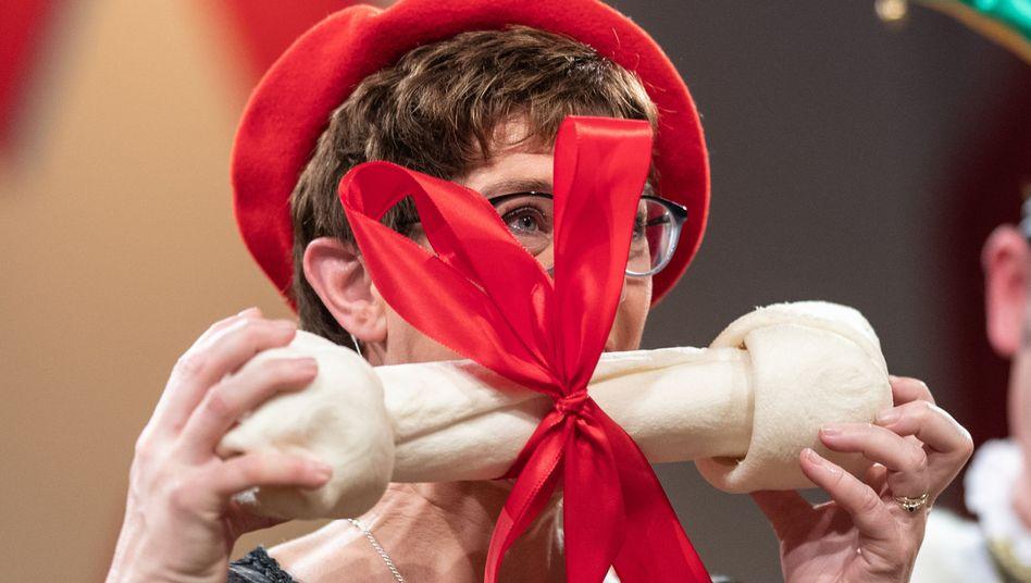 Annegret Kramp-Karrenbauer beißt in einen Plastikknochen.