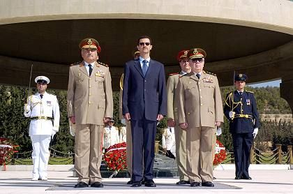 Syrian President Bashar Assad (center) and military officials: For months now, Assad has been a thorn in the side of the US government.