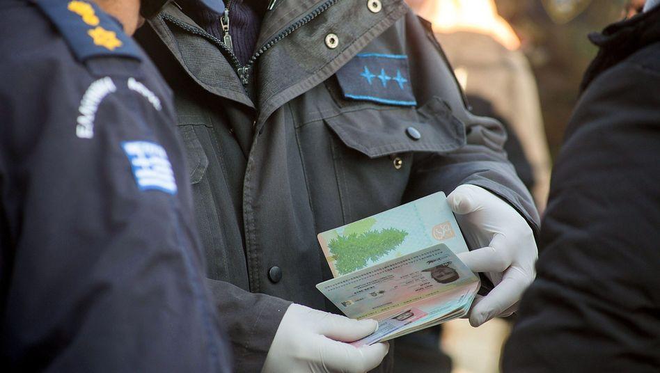 """Griechische Polizisten kontrollieren die Papiere eines Flüchtlings (18. Dezember): """"Natürlich ein Sicherheitsrisiko"""""""
