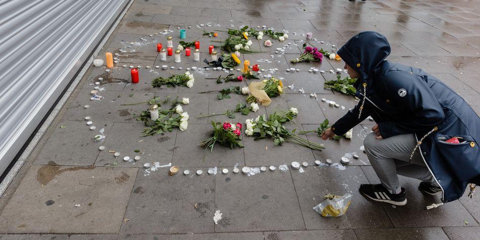 Eine Frau legt in Hamburg Blumen vor dem Supermarkt-Tatort ab