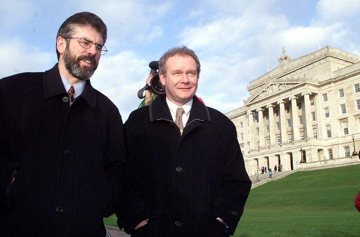 Partner Gerry Adams, Martin McGuinness (rechts, Foto von 1999): Adams leugnet bis heute, jemals PIRA-Mitglied gewesen zu sein. McGuinness gab nie zu, dass er sogar Chef des »Armeerates« gewesen sein mag. Öffentlich handelten sie als Vertreter von »Ballot and Bullet«.