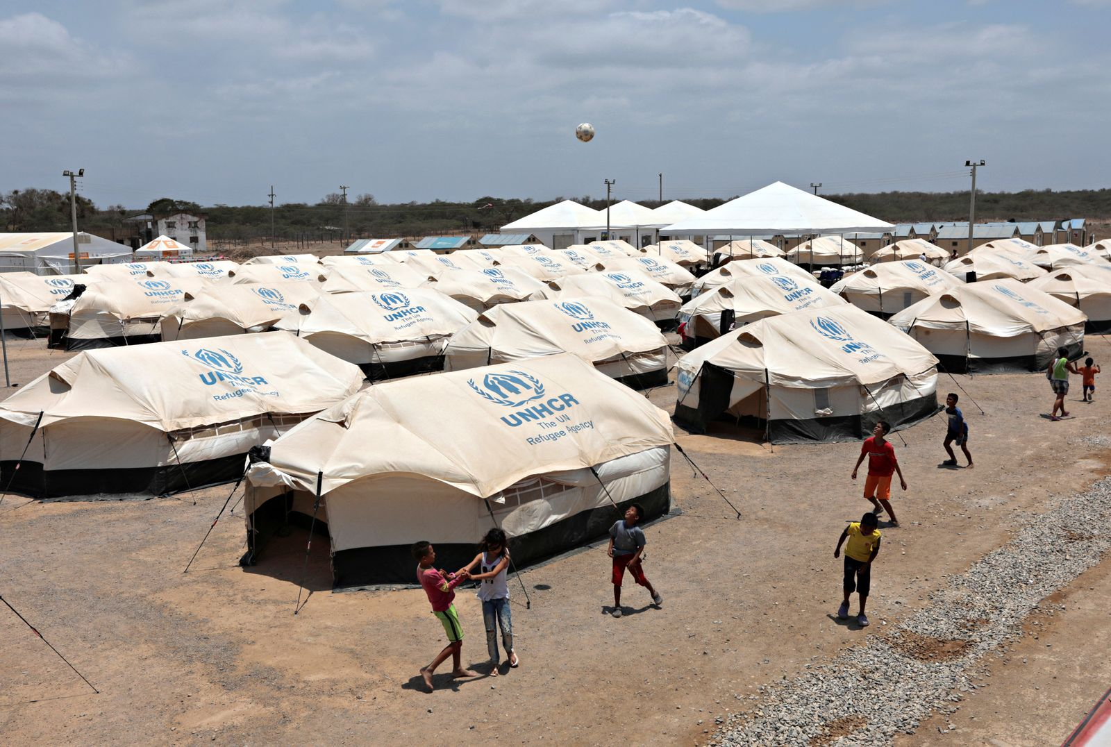 Venezuelan migrant children play soccer in a camp run by the UN refugee agency UNHCR in Maicao