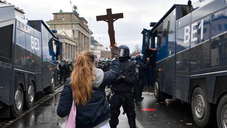 Eine Demonstrantin hält in Berlin bei den Protesten gegen das Infektionsschutzgesetz einem Polizisten ein Kreuz entgegen