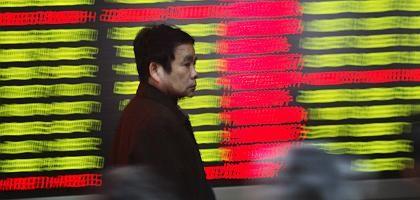 Spaziergänger vor einer Kurstafel in Shanghai: 60 Prozent verloren