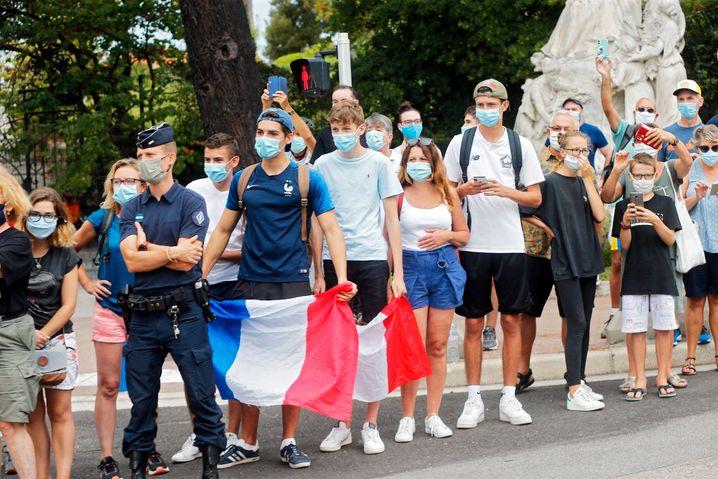 Mit Maske und Fahne: Tour-Fans am Straßenrand