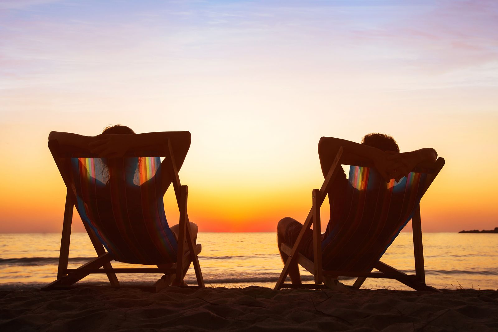 happy couple relaxing in beach hotel at sunset, honeymoon