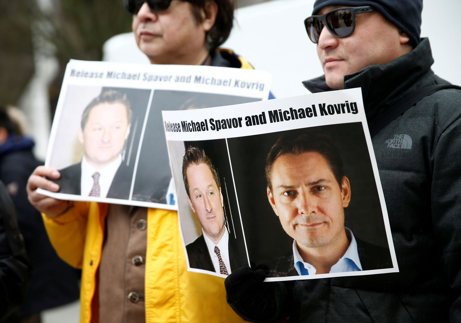 FILE PHOTO: People hold signs calling for China to release Canadian detainees Spavor and Kovrig during an extradition hearing for Huawei Technologies Chief Financial Officer Meng Wanzhou at the B.C. Supreme Court in Vancouver