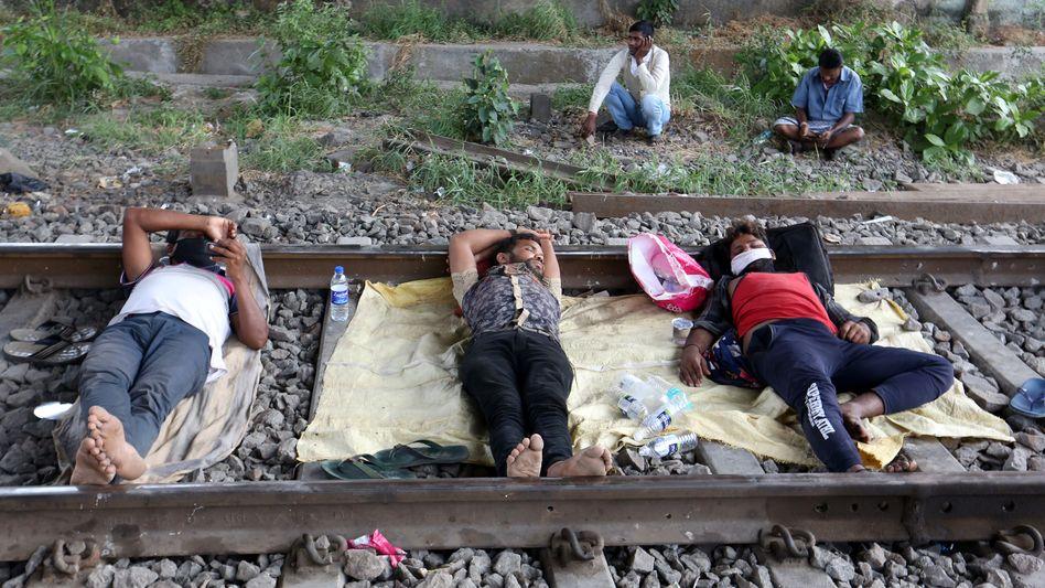 Wanderarbeiter ruhen sich im April 2020 auf Schienen aus