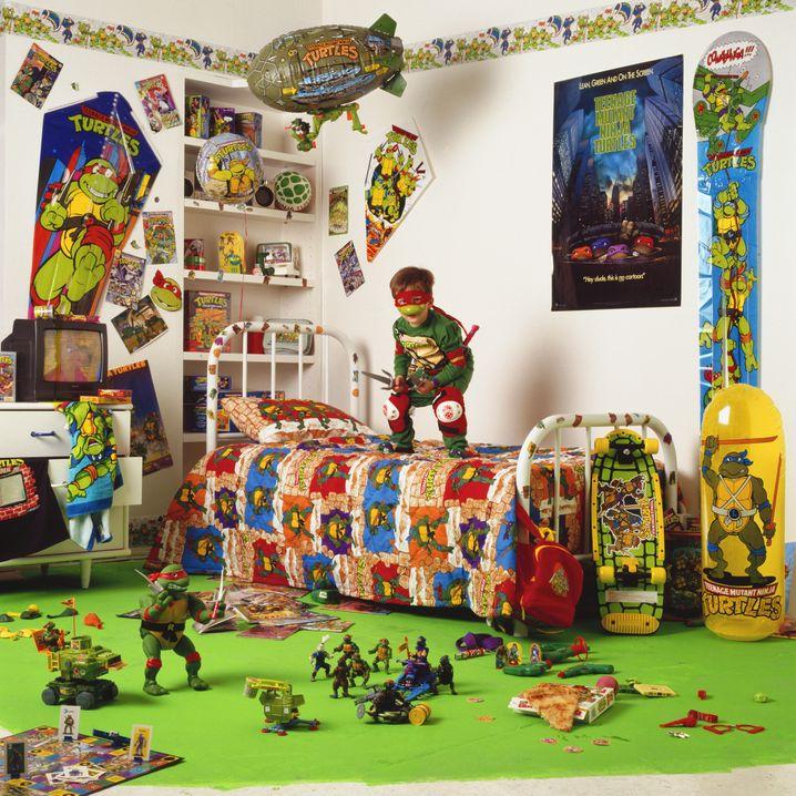 """Ein Junge inmitten einer Sammlung von """"Turtles""""-Merchandise. Ende der Achtzigerjahre überzeugte der Lizenzierungsagent Martin Freedman die Eastman und Laird, ihre Geschöpfe zu vermarkten. Das Ergebnis waren Unmengen von Spielzeug, das besonders bei Kindern reißenden Absatz fand."""