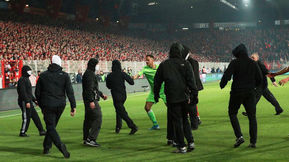 Nach dem Berlin-Derby drängten Vermummte Union-Ultras aufs Spielfeld. Torwart Rafal Gikiewicz stellte sich ihnen entgegen