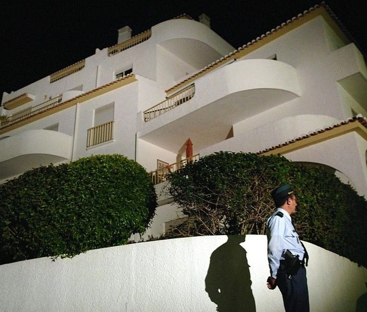 A police officer can be seen standing in front of the holiday resort in Praia da Luz in 2007 where Maddie McCann disappeared.