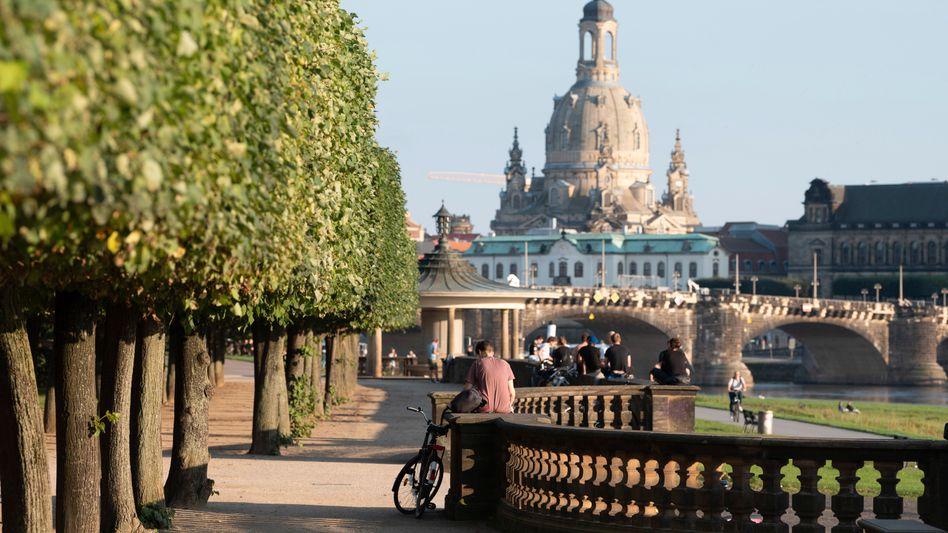 Blick auf die Frauenkirche: Passanten bei sommerlichem Wetter am Ufer der Elbe in Dresden