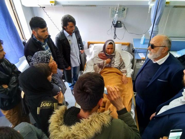 Der Minister für Schifffahrt und Inseln, Panagiotis Kouroumblis (r.) im Krankenhaus von Samos, mit der einzigen Überlebenden der afghanischen Familie und deren Angehörigen