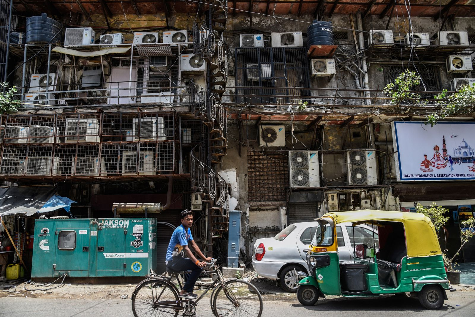A man cycles past a facade with rows of air conditioners on a hot summer afternoon in New Delhi.