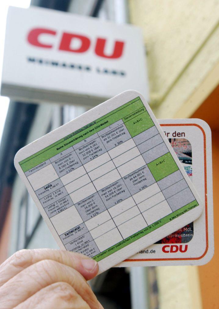 Ein in der Form eines Steuerformulars gestalteter Bierdeckel, aufgenommen am Montag (08.03.2004) vor dem Haus der Kreisgeschäftsstelle der CDU im thüringischen Apolda zur Illustration der aktuellen Steuerdebatte. Nachdem der CDU-Finanzexperte Friedrich Merz seinerzeit ein so radikal vereinfachtes Steuerkonzept ankündigte, bei dem jeder Bürger seine eigene Steuererklärung selbst auf einem Formular in der Größe eines Bierdeckels ausfüllen kann, haben die jüngsten Reformbeschlüsse der Union zu Steuern und Arbeitsmarkt vielfach Enttäuschung ausgelöst. Obwohl die ursprünglich erwartete Vereinfachung des Steuerrechts nach der Einigung von CDU und CSU erst einmal ausbleibt, wollen die Christdemokraten in Apolda im Kreis Weimarer Land mit ihren eigens bedruckten Bierdeckeln in den Landtagswahlkampf ziehen. Foto: Jan-Peter Kasper dpa/lth (zu dpa 4172 vom 08.03.2004) | Verwendung weltweit