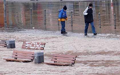 Kleine Frankfurter haben ihren Spaß: Der Main hat die Uferpromenade unter Wasser gesetzt