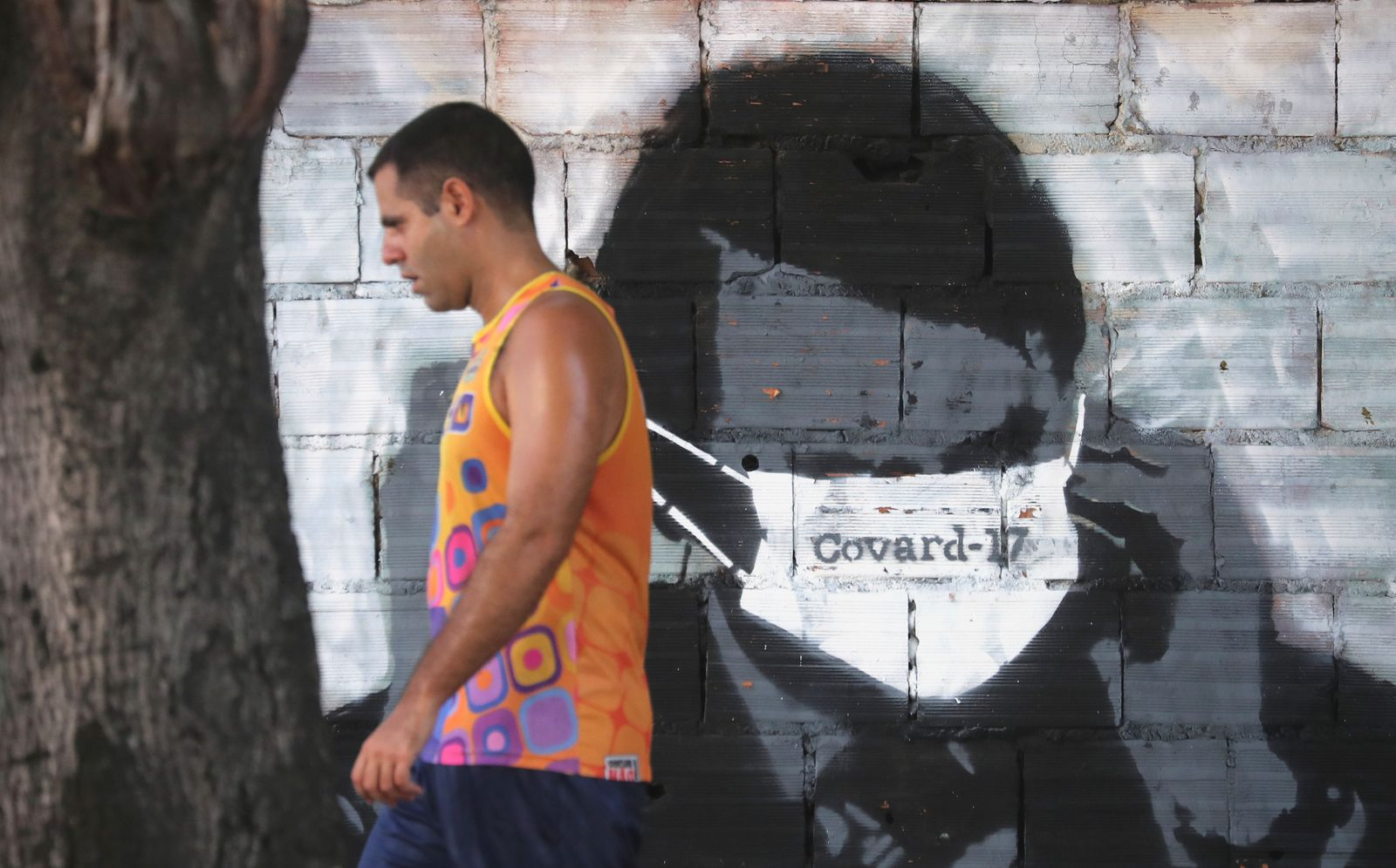 Man walks past by a graffiti depicting Brazilian president Bolsonaro adjusting his protective face mask during the coronavirus disease (COVID-19) outbreak, in Rio de Janeiro