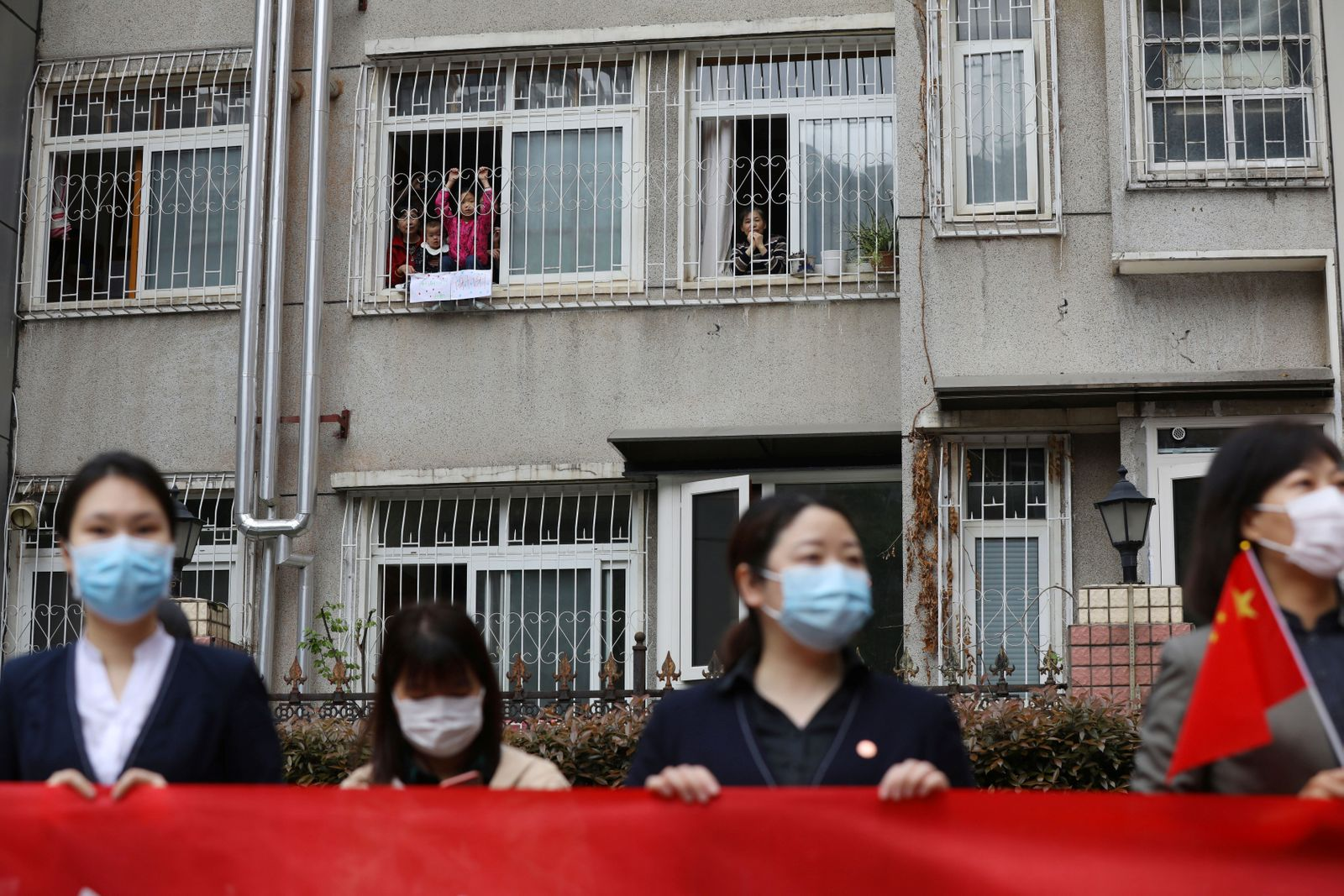 Residents bid farewell from their homes to a medical team from Guizhou province who is leaving Wuhan, following the novel coronavirus disease (COVID-19) outbreak, in Hubei