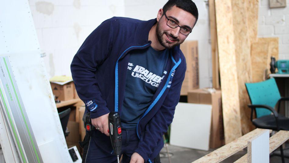 Hasan Aydin schraubt bei seinem neuen Ausbilder Regale zusammen
