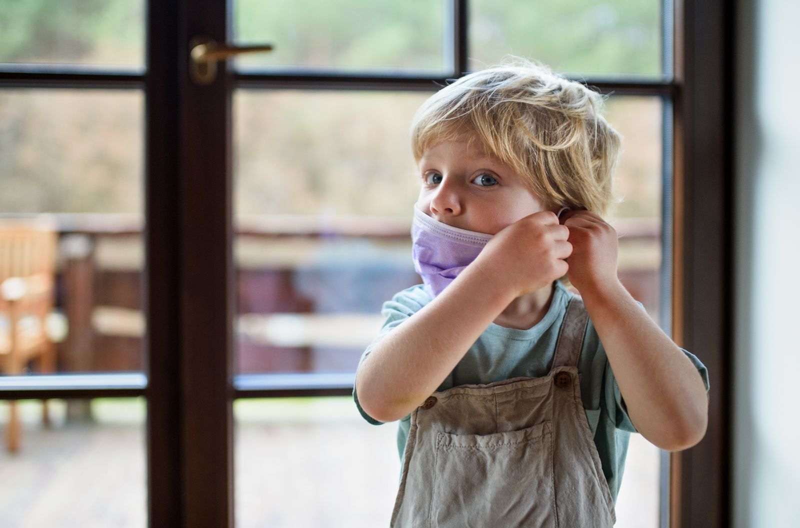 Front view of unhappy small boy with face mask at home.