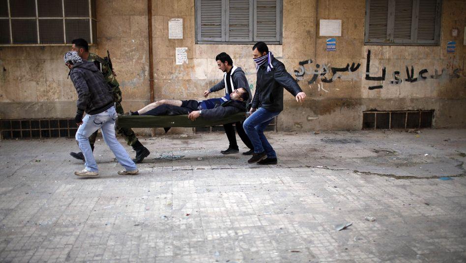 Ein Verletzter wird in Aleppo weggetragen: Tausende Tote im Bürgerkrieg