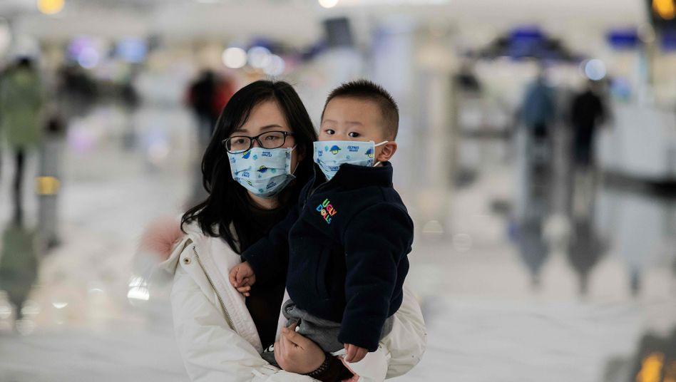 Eine Frau schützt sich und ihr Kind am Flughafen von Peking mit einer Atemmaske