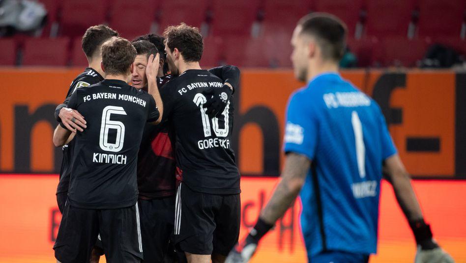 Robert Lewandowski wird nach seinem Elfmetertreffer von seinen Mitspielern geherzt