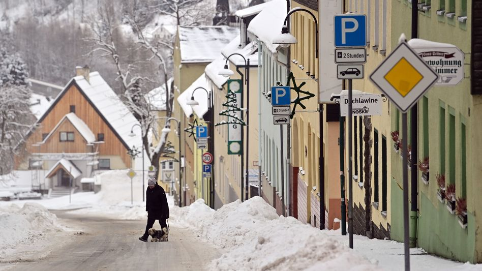 Winter im Erzgebirge: Eine Frau geht in Oberwiesenthal über eine leere Straße im Zentrum der Stadt