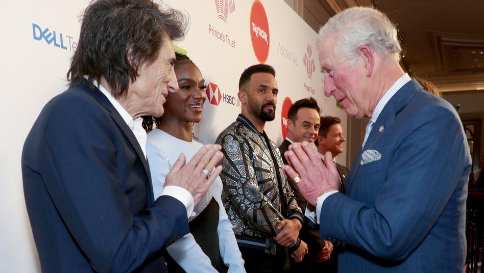 """Im Gebäude klappte es dann:Prinz Charles begrüßt Rolling-Stones-Gitarrist Ronnie Wood mit einem """"Namaste"""""""