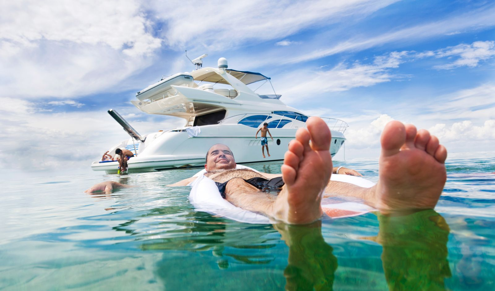 Man floating on air bed with boat in background
