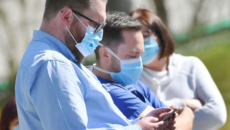 Menschen mit Mundschutzmaske und Mobiltelefon (Archivbild)