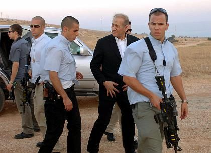 """Israeli Prime Minister Ehud Olmert accompanied by bodyguards: """"We will win at the end."""""""