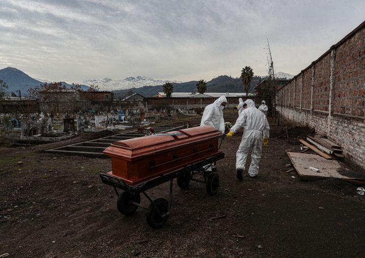 Friedhofsmitarbeiter ziehen den Sarg eines verstorbenen Corona-Patienten in Santiago de Chile (Foto vom Vortag)