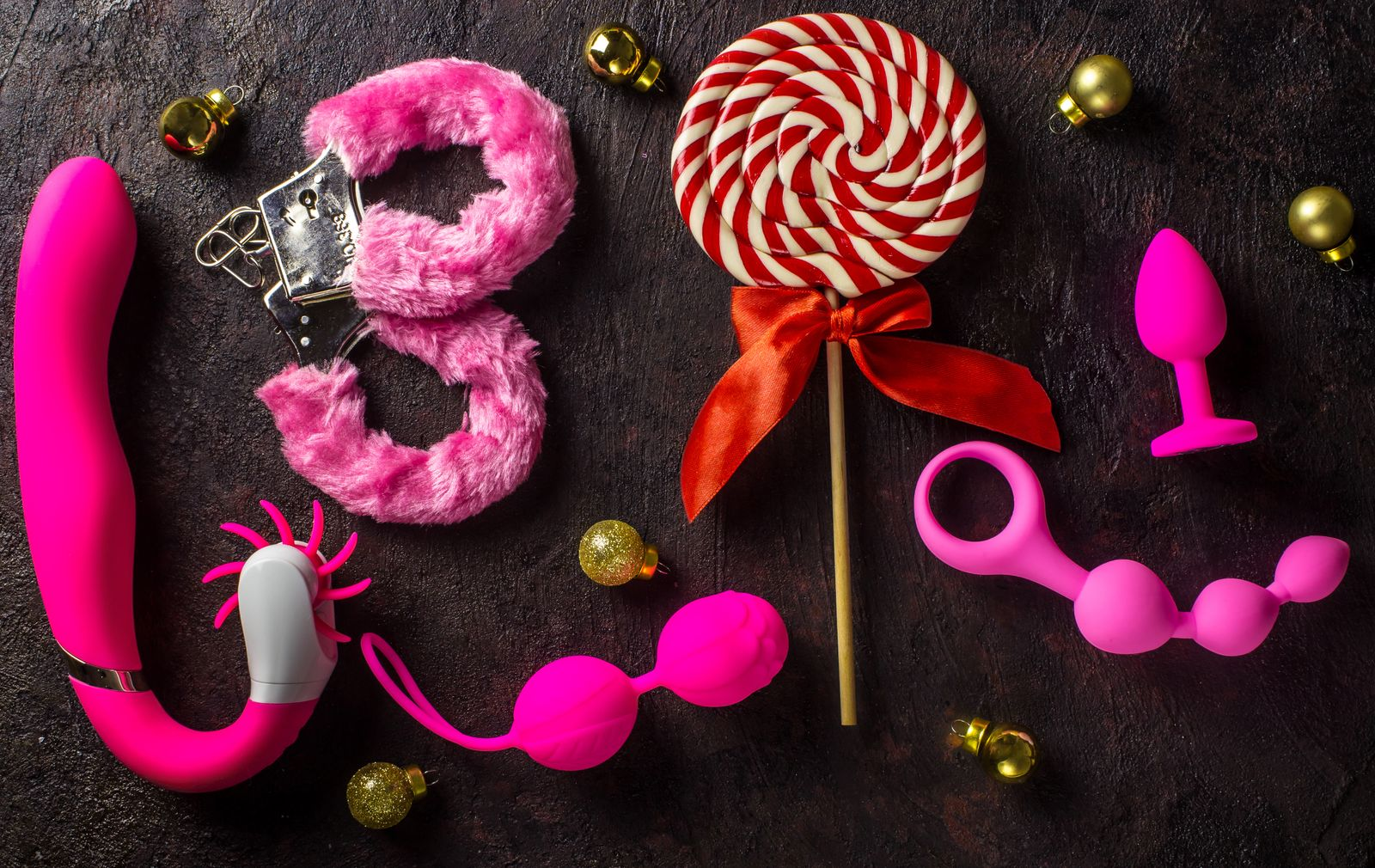Various sex toys (anal balls, vibrator, fur handcuffs and others), christmas balls and candy.