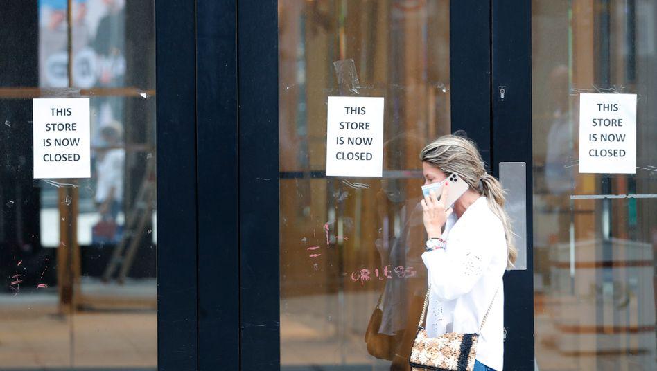 Passantin vor einem geschlossenen Geschäft in London
