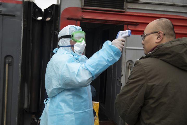 Ein Mediziner kontrolliert einen Reisenden aus China am Bahnhof in Moskau.