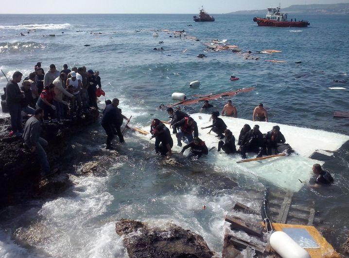 Flüchtlinge, die auf dem zerschellten Boot waren, kommen am Strand von Rhodos an