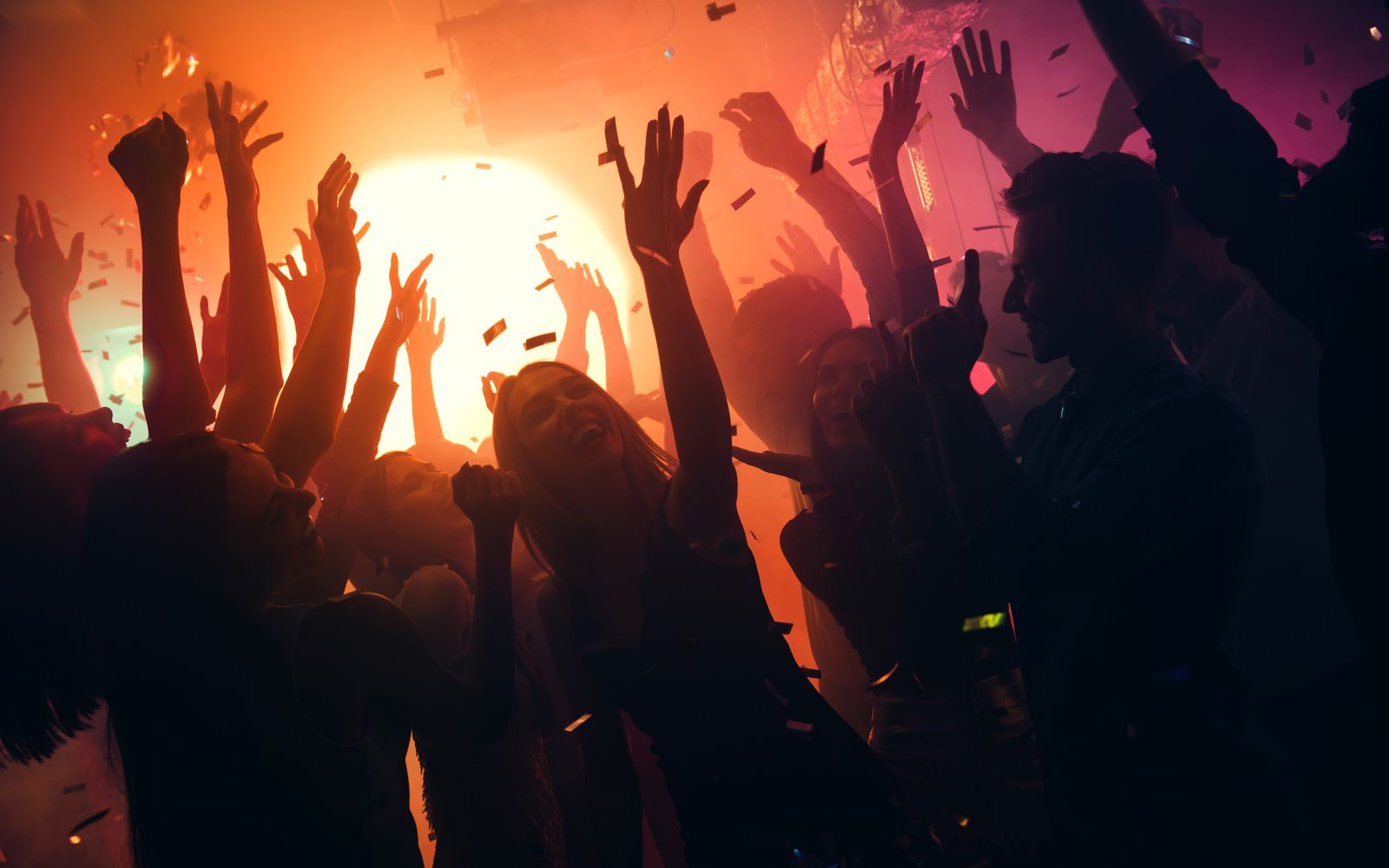Photo of many party people buddies dancing yellow lights confetti flying everywhere nightclub event hands raised up wear shiny clothes