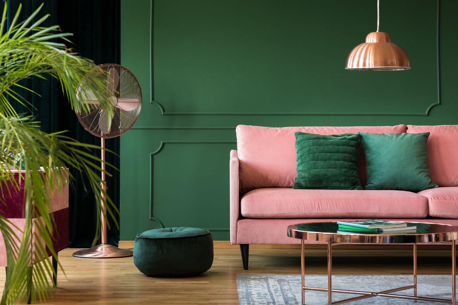 Copper lamp and table in a green living room interior. Real photo