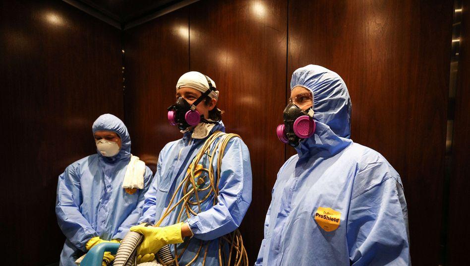 Reinigungskräfte stehen mit Schutzmasken in einem Aufzug eines öffentlichen Gebäudes in Hunt Valley (Maryland)